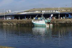 El barco de pesca del blanco y de la turquesa atracó junto al embarcadero con el fondo del almacén Fotografía de archivo libre de regalías