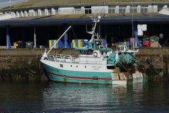 El barco de pesca del blanco y de la turquesa atracó junto al embarcadero con el fondo del almacén Imagen de archivo