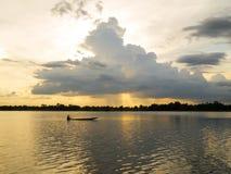 El barco de pesca en el río con puesta del sol se enciende Fotos de archivo