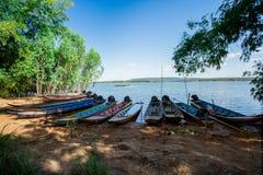 El barco de pesca en orilla o la playa al lado del lago acumula debajo del cielo azul en Sunny Day Fotografía de archivo libre de regalías