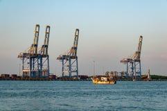 El barco de pesca pone hacia fuera al mar del puerto de Cochi, con industria pesada en el fondo fotos de archivo