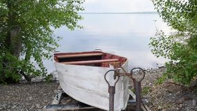 El barco de pesca viejo del rowing se ata y se abandona con la cadena a la orilla del río almacen de metraje de vídeo