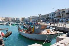 El barco de pesca viejo parqueó en el puerto de la ciudad foto de archivo