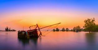 El barco de pesca viejo volcó en el mar en la puesta del sol en Phuket Foto de archivo libre de regalías