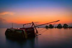 El barco de pesca viejo volcó en el mar en la puesta del sol en Phuket Fotos de archivo