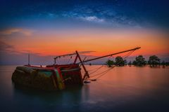 El barco de pesca viejo volcó en el mar con la vía láctea en la puesta del sol adentro Imágenes de archivo libres de regalías