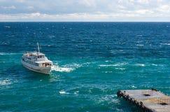 El barco de placer está amarrando a un pequeño embarcadero Foto de archivo libre de regalías