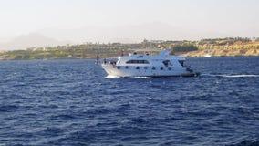 El barco de placer flota en las ondas del Mar Rojo en el fondo de la costa y de playas en Egipto almacen de video