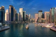 El barco de placer mueve a lo largo de un canal el puerto deportivo de Dubai Imágenes de archivo libres de regalías
