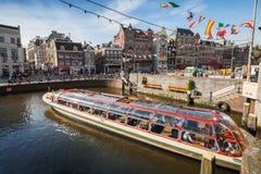 El barco de visita turístico de excursión pasa a través del canal en Amsterdam Imágenes de archivo libres de regalías
