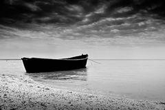 El barco del negro de la pesca cerca de la orilla Fotografía de archivo