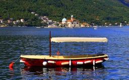 El barco del rojo navega en la bahía de Kotor, Montenegro Imagen de archivo