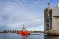 El barco del tirón ayuda a maniobrar una nave grande Imagenes de archivo