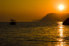 El barco en el mar con puesta del sol anaranjada Foto de archivo libre de regalías