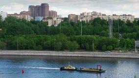 El barco está en el río en la ciudad metrajes