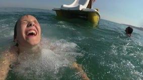 El barco feliz de la muchacha arranca la colina en el mar, visión desde el agua almacen de video