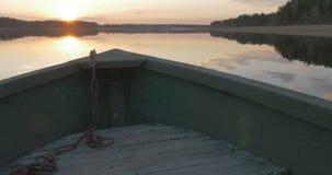 El barco flota en el lago en la puesta del sol almacen de video