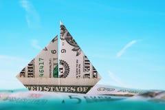 El barco hecho de una cuenta del uno-dólar flota en el océano imágenes de archivo libres de regalías