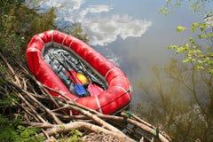 El barco inflable rojo con los remos transporta en balsa para transportar en balsa a lo largo de un r?o foto de archivo libre de regalías
