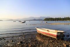 El barco permanece en una playa de piedra Fotografía de archivo libre de regalías