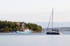 El barco pesquero para las devoluciones de la extracción del calamar en la navegación de la madrugada más allá del yate verde de  fotografía de archivo