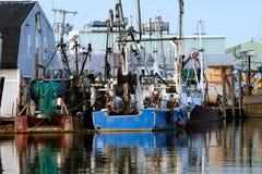 El barco rastreador azul y rojo colorido de la pesca sienta marcha lenta en un h protegido imagenes de archivo