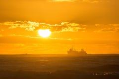 El barco rastreador bañado en luz de oro pasa delante de la puesta del sol fotos de archivo libres de regalías