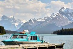 El barco tranquilo espera en Jasper Lake con las montañas Nevado en el fondo Fotos de archivo libres de regalías
