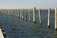 El barco vacío alineado se desliza/las pilas en la bahía Fotografía de archivo