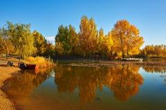 El barco y la orilla del lago otoñal de los árboles Imagenes de archivo