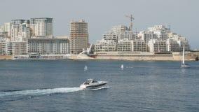 El barco, yate navega en el fondo de la ciudad La Valeta en Malta Tiro ancho, en el fondo de casas nuevamente construidas almacen de video