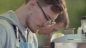 El barista del hombre joven pone los granos de café en la máquina en el festival exterior metrajes