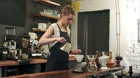 El barista femenino joven en cafetería moderna de moda del café vierte el agua hirvienda sobre los argumentos de café que hacen u metrajes