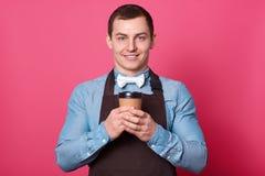 El barista masculino atractivo lleva la camisa azul, bowtie blanco y el delantal marrón, sostiene la taza de café de papel, tiene fotografía de archivo