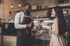El barista masculino ayuda a una muchacha a elegir un postre imagen de archivo libre de regalías