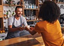 El barista masculino sirve la taza de café al cliente femenino en café imagenes de archivo