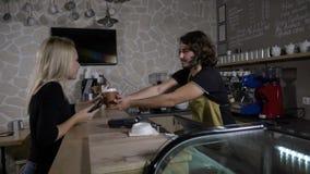 El barista masculino sirve y liga con un cliente femenino hermoso que pague con el smartphone app en una cafetería en la cámara l almacen de video