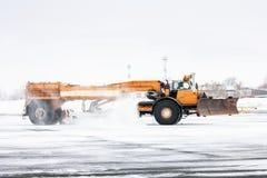 El barrendero del campo de aviación limpia la pista Imagen de archivo libre de regalías