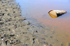 El barril oxidado contamina el río Fotos de archivo