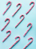 El bastón de caramelo de la Navidad mintió uniformemente en fila en azul Endecha plana y visión superior imagenes de archivo