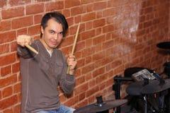 El batería con el tambor se pega en sus manos que juegan los tambores electrónicos i fotografía de archivo libre de regalías