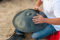 El batería en la acción individuo que se sienta en la playa y el jugar handpan o la caída de la arena La caída es tambor étnico t foto de archivo