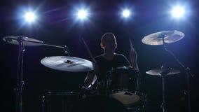 El batería juega la melodía en los tambores enérgico Fondo negro Luz posterior Silueta almacen de video