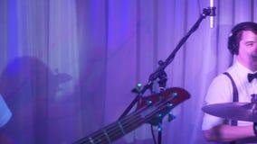 El batería juega la melodía en los tambores enérgico Mudanza de la cámara desde el batería al guitarrista metrajes