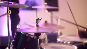 El batería juega los palillos en los tambores Los golpes teclean los palillos en las placas y teclear el sistema almacen de video