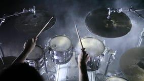 El batería juega los tambores en un hangar Fume el fondo metrajes