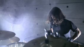 El batería juega los tambores en un hangar Fume el fondo almacen de video