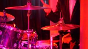 El batería juega el sistema del tambor en el club almacen de metraje de vídeo