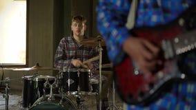 El batería loco en traje juega la canción El hombre joven enojado está jugando en música de los tambores con el guitarrista en el almacen de video