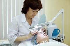El Beautician en salón limpia la piel de la mujer. Imágenes de archivo libres de regalías